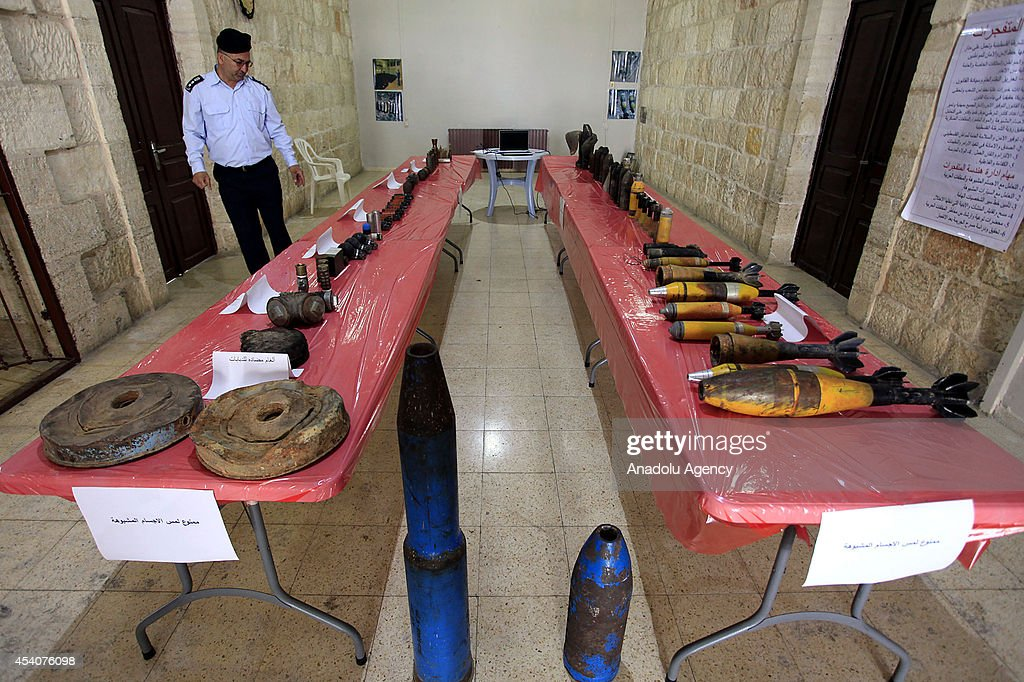 A Palestinian colonel who works at the exhibition, examines ammunitions, that Israel army use on the attacks on Gaza, in Ramallah, West Bank on 24 August, 2014. Gas bomb, hand grenade, plastic bullet, real bullet, rocket and other ammunitions of Israel army are displayed at the exhibition.