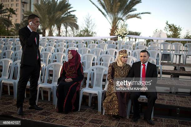 Palestinian couples are pictured on January 28 during a mass wedding ceremony attended by Palestinian Authority President Mahmud Abbas in the West...