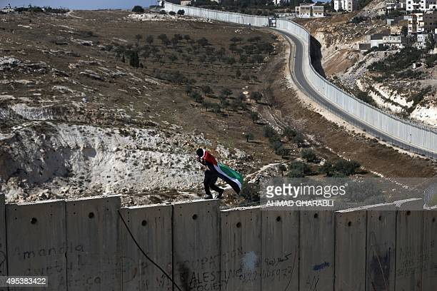 A Palestinian covered with national flag walks on top of the Israeli controvertial separation wall separating the West Bank city of Abu Dis from east...