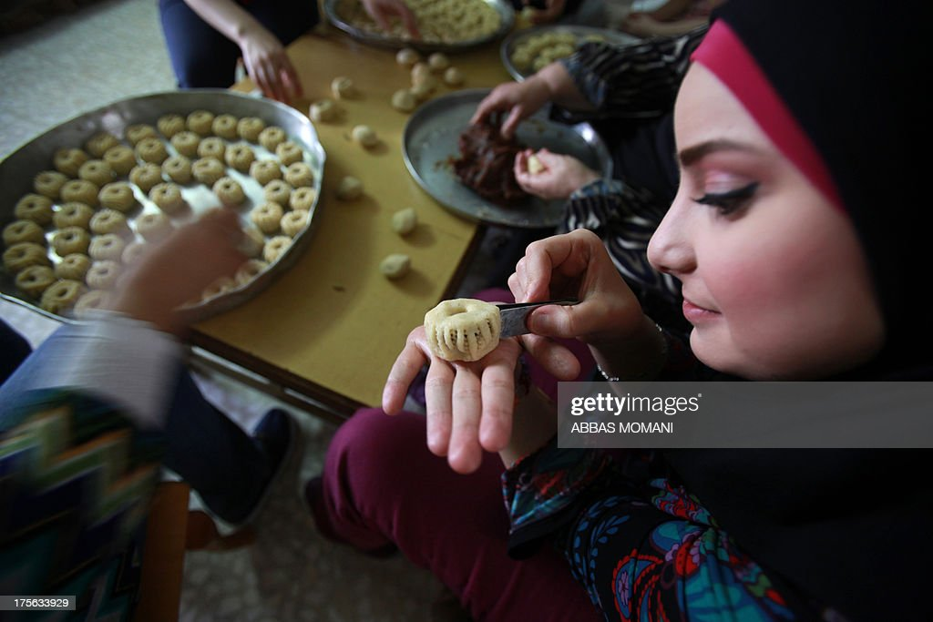 A Palestinian decorates traditional biscuits popular on the occasion of Eid al-Fitr at her home in the West Bank city of Ramallah, on August 5, 2013. Muslims around the world are preparing to celebrate the Eid al-Fitr holiday, which marks the end of the fasting month of Ramadan. Preparations include buying new clothes, toys and special sweets.