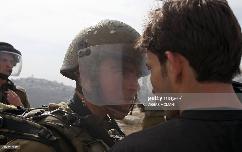 A Palestinian demonstrator confronts an Israeli soldier during a protest against the confiscation of Palestinian land by Israel in the West Bank village of Nabi Saleh near Ramallah on November 2, 2012.
