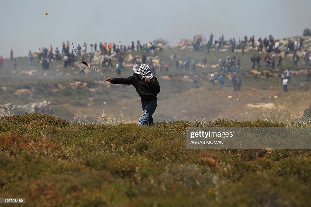 A Palestinian demonstrator from the West Bank village of Deir Jarir, northeast of Ramallah, uses a sling shot to trhow rocks towards Israeli security forces during clashes following a march against construction on their land by members of the Jewish settlement of Ofra on April 26, 2013.