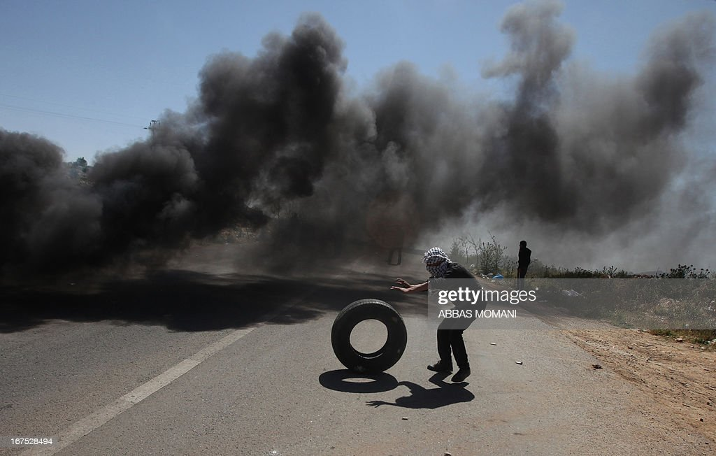 A Palestinian demonstrator from the West Bank village of Deir Jarir, northeast of Ramallah, rolls a tyre near rising smoke during clashes with Israeli soldiers following a march against construction on their land by members of the Jewish settlement of Ofra on April 26, 2013.