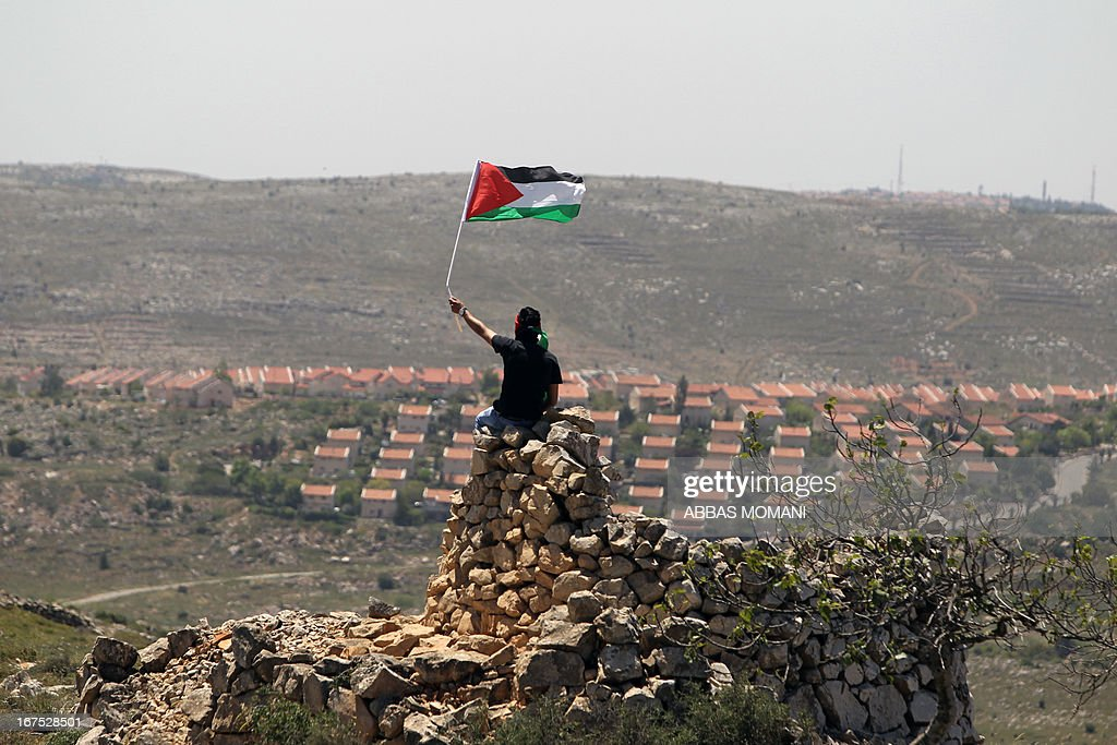 A Palestinian demonstrator from the West Bank village of Deir Jarir, northeast of Ramallah, waves his national flag as he sits on a pile of rocks during clashes with Israeli soldiers following a march against construction on their land by members of the Jewish settlement of Ofra on April 26, 2013.