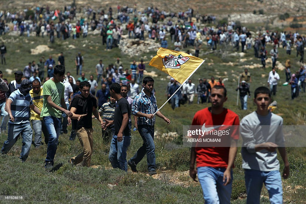 A Palestinian demonstrator from the West Bank village of Deir Jarir, northeast of Ramallah, waves the Fatah movement flag as he marches with fellow protestors against construction on their land by members of the nearby Jewish settlement of Ofra on April 26, 2013.