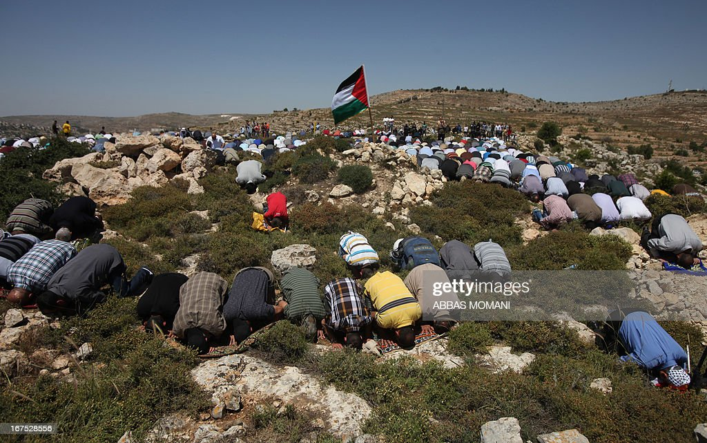 A Palestinian demonstrator from the West Bank village of Deir Jarir, northeast of Ramallah, waves his national flag as as others pray prior to clashes with Israeli soldiers following a march against construction on their land by members of the nearby Jewish settlement of Ofra on April 26, 2013. AFP PHOTO / ABBAS MOMANI