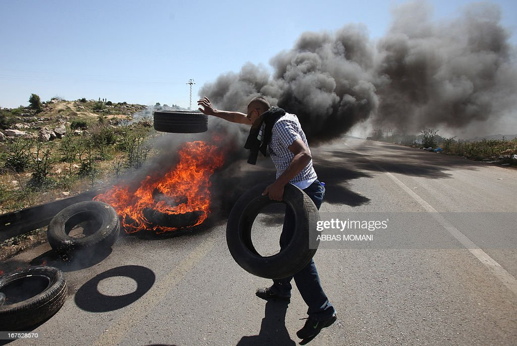 A Palestinian demonstrator from the West Bank village of Deir Jarir, northeast of Ramallah, burns tyres during clashes with Israeli soldiers following a march against construction on their land by members of the nearby Jewish settlement of Ofra on April 26, 2013.