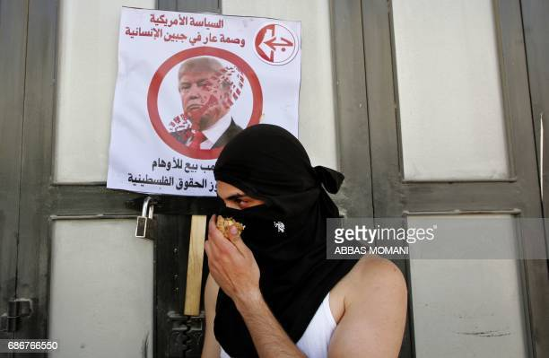 A Palestinian demonstrator holds an onion used against tear gas in front of a placard bearing a picture of US President Donald Trump denouncing his...