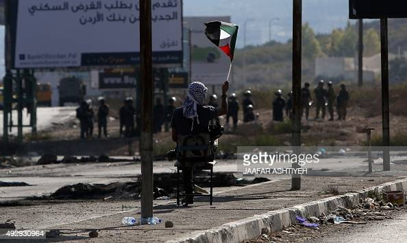 A Palestinian demonstrator is seen waving the national flag during clashes with Israeli border guards at the Hawara checkpoint south of the West Bank...