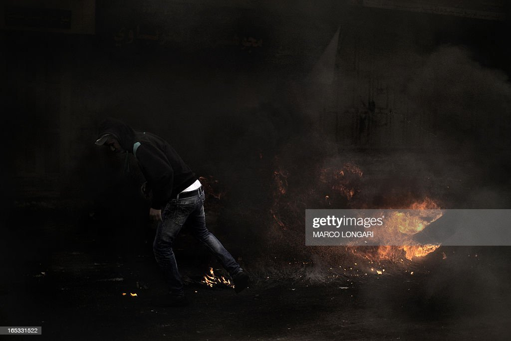 A Palestinian demonstrator kicks a flaming tire during clashes with the Israeli army in the West Bank city of Hebron on April 3, 2013. Palestinians across the West Bank and Gaza were observing a general strike, with prisoners refusing food to mourn the death of a fellow inmate in an Israeli jail. AFP PHOTO/MARCO LONGARI