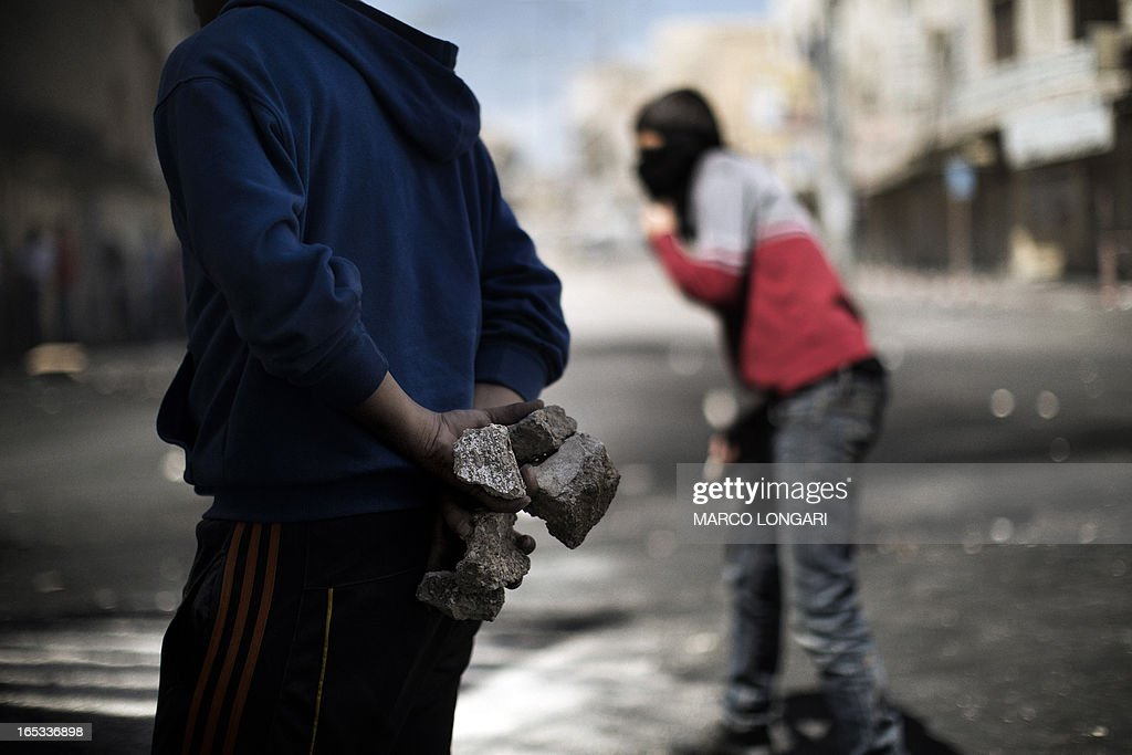 A Palestinian demonstrator prepare rocks to be thrown during clashes with the Israeli army in Hebron April 3, 2013. Palestinians across the West Bank and Gaza were observing a general strike, with prisoners refusing food to mourn the death of a fellow inmate in an Israeli jail. AFP PHOTO/MARCO LONGARI