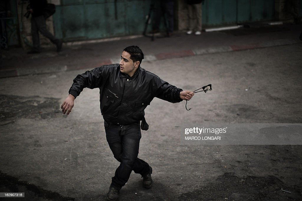 A Palestinian demonstrator prepares to hurl stones towards Israeli troops during clashes in the old city of Hebron on March 1, 2013 following a protest demanding the reopening of Shuhada Street, the one-time heart of the city, which has been declared off-limits to Palestinians and can only be used by Jewish settlers. AFP PHOTO/MARCO LONGARI