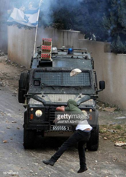 A Palestinian demonstrator throws a rock at an Israeli military vehicle during clashes following a protest against the expropriation of Palestinian...