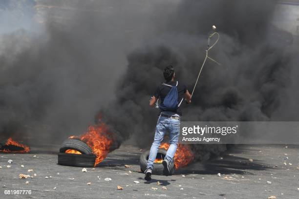 Palestinian demonstrator throws a stone with a slingshot in response to Israeli security forces' intervention in a demonstration in support of hunger...