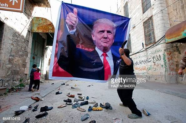 Palestinian demonstrator throws an old shoe at a poster of US President Donald Trump as they protest against his support of Israel and demand for the...