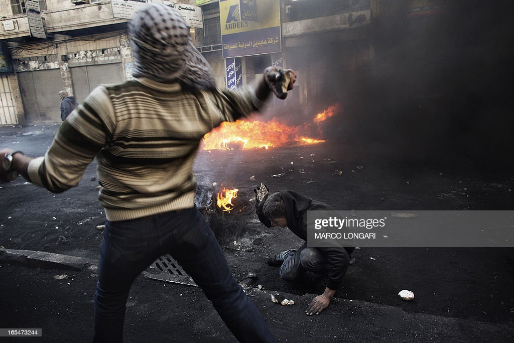 A Palestinian demonstrator throws stones towards Israeli security forces as his comrade breaks stones on the ground during clashes in the West Bank city of Hebron on April 4, 2013. Clashes rocked the West Bank as thousands attended the funerals of a prisoner and two teenagers shot dead by Israeli troops and Palestinian president Mahmud Abbas said the killings jeopardised US efforts to rekindle peace talks. AFP PHOTO/MARCO LONGARI