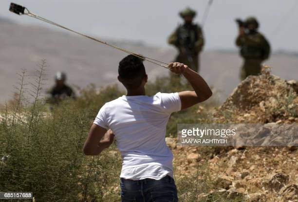 A Palestinian demonstrator uses a sling shot to throw stones during clashes with Israeli forces following a protest in support of Palestinian...