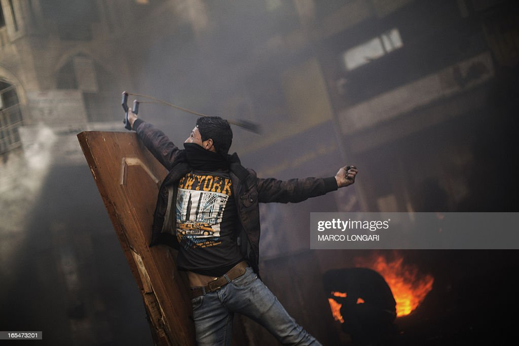 A Palestinian demonstrator uses a sling shot to throw stones from behind a barricade during clashes with Israeli security forces in the West Bank city of Hebron on April 4, 2013. Clashes rocked the West Bank as thousands attended the funerals of a prisoner and two teenagers shot dead by Israeli troops and Palestinian president Mahmud Abbas said the killings jeopardised US efforts to rekindle peace talks. AFP PHOTO/MARCO LONGARI