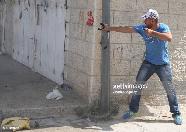Palestinian demonstrator uses a slingshot in response to Israeli security forces' intervention with tear gas bomb during a demonstration to protest...
