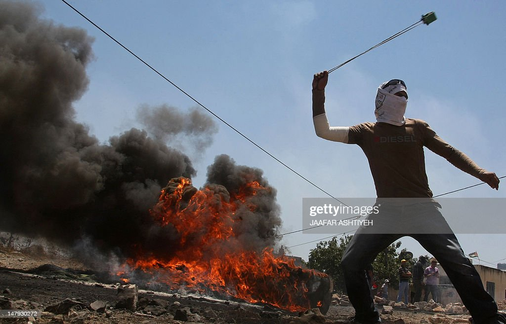 A Palestinian demonstrator uses a slingshot to hurl stones towards Israeli troops during a protest against the expropriation of Palestinian land by Israel in the West Bank village of Kafr Qaddum near Nablus on July 6, 2012.