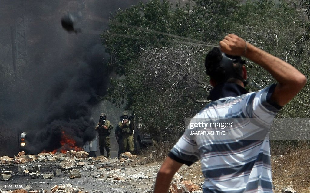 A Palestinian demonstrator uses a slingshot to hurl stones towards Israeli troops during a protest against the expropriation of Palestinian land by Israel in the West Bank village of Kafr Qaddum near Nablus on July 27, 2012.