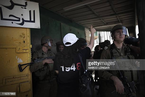 A Palestinian demonstrator wearing a tshirt referring to the creation of the Israeli State in 1948 yells at Israeli soldiers during a protest marking...