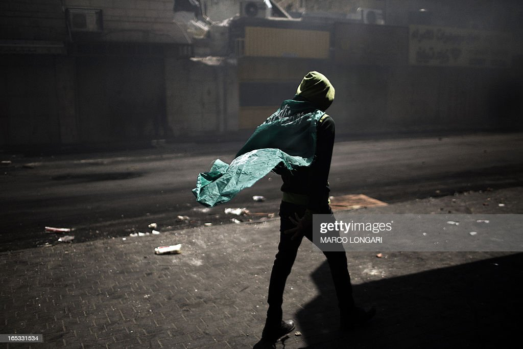 A Palestinian demonstrator wears a Hamas flag during clashes with the Israeli army in Hebron April 3, 2013. Palestinians across the West Bank and Gaza were observing a general strike, with prisoners refusing food to mourn the death of a fellow inmate in an Israeli jail.