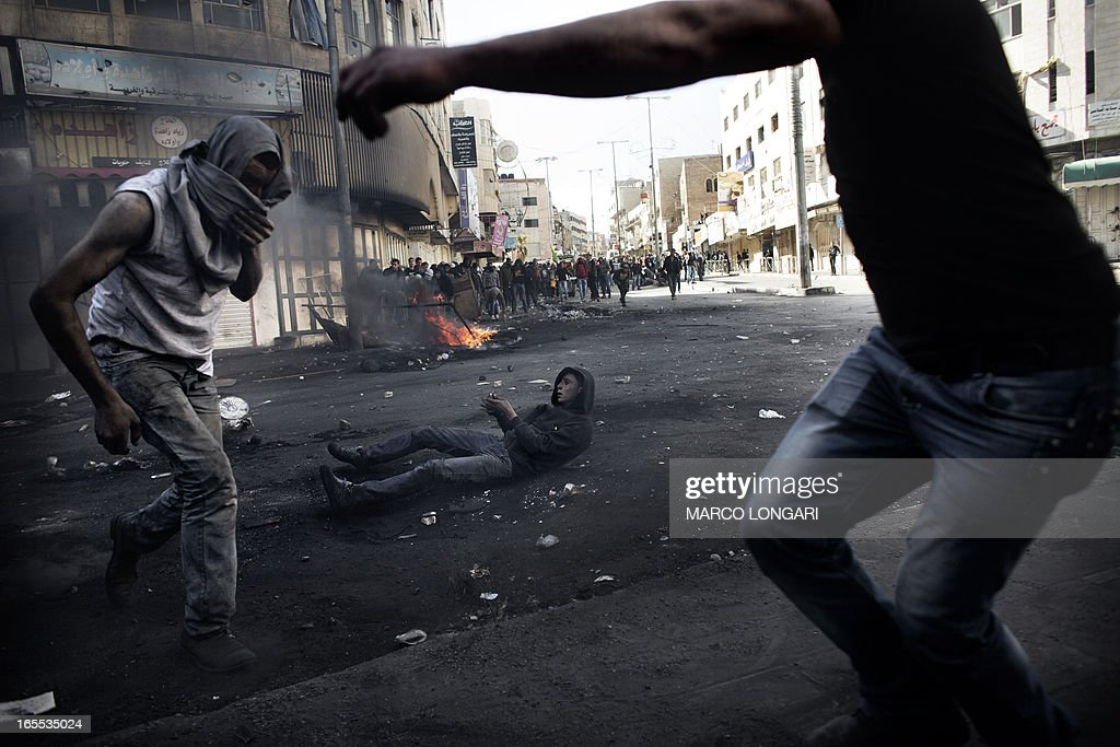 Palestinian demonstrators are seen during clashes with Israeli security forces in the West Bank city of Hebron on April 4, 2013. Clashes rocked the West Bank as thousands attended the funerals of a prisoner and two teenagers shot dead by Israeli troops and Palestinian president Mahmud Abbas said the killings jeopardised US efforts to rekindle peace talks. AFP PHOTO/MARCO LONGARI