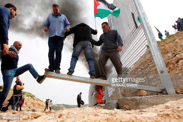 TOPSHOT Palestinian demonstrators attempt to damage an iron fence setup by Israeli security forces between the Palestinian village of Beit Jala and...