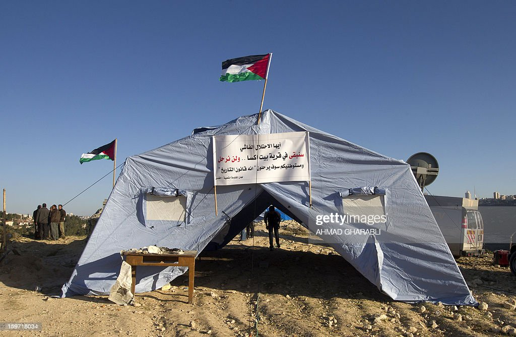 Palestinian demonstrators gather next to tents flying their national flag in the West Bank village of Beit Iksa, between Ramallah and Jerusalem, on January 19, 2013, during the second consecutive day of protests against Israel's intention to confiscate land. AFP PHOTO/AHMAD GHARABLI