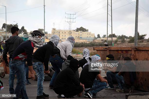 Palestinian demonstrators hiding behind the trash container to protect them from Israeli army fire on October 9 2015 The leader in the Gaza Strip of...