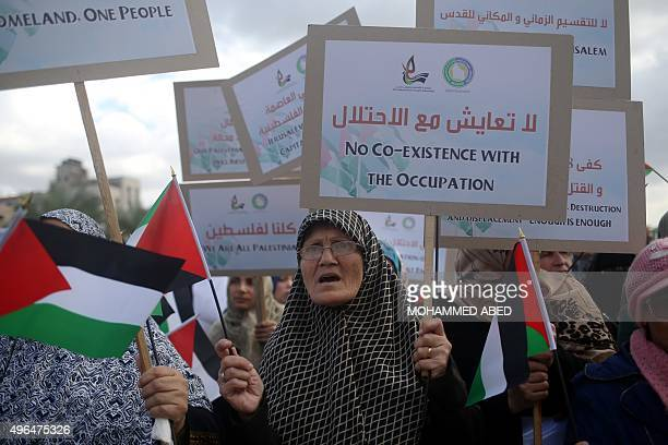 Palestinian demonstrators hold their national flag and banners during an antiIsrael protest in Gaza City on November 10 2015 Attacks and violent...