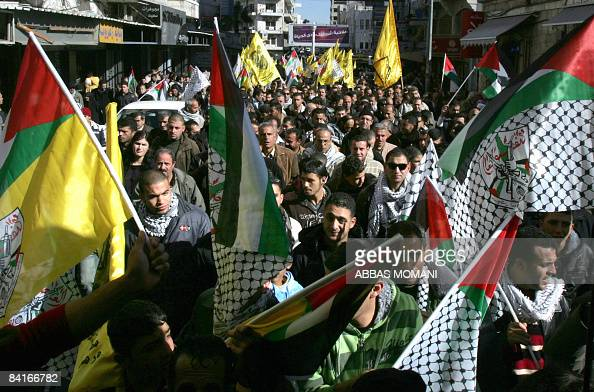 Palestinian demonstrators hold up their national flag and Fatah flags as they chant anti Israeli slogans during a protest against Israel's military...
