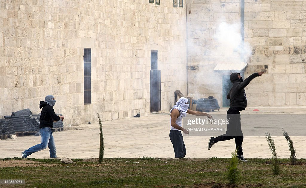 Palestinian demonstrators hurl rocks at Israeli border police during a protest at Jerusalem's Al-Aqsa mosque following a protest in solidarity with hunger-striking Palestinian prisoners on February 22, 2013. Palestinians demanding the release of hunger-striking prisoners clashed with Israelis in the West Bank and east Jerusalem, as three fasting inmates were taken to hospitals. AFP PHOTO/AHMAD GHARABLI