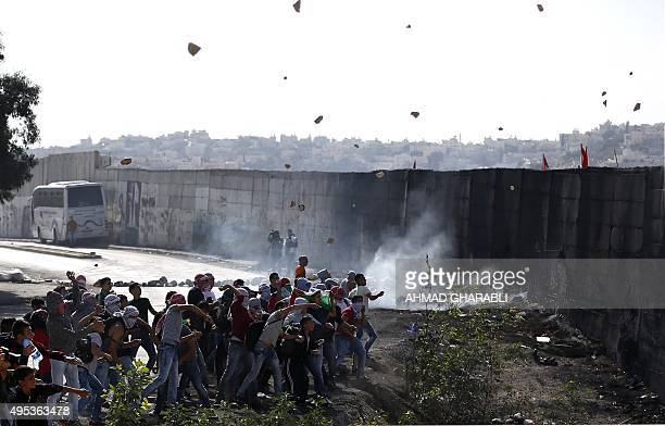 Palestinian demonstrators hurls rocks towards Israeli borderguards next to the Israeli controvertial separation wall separating the West Bank city of...