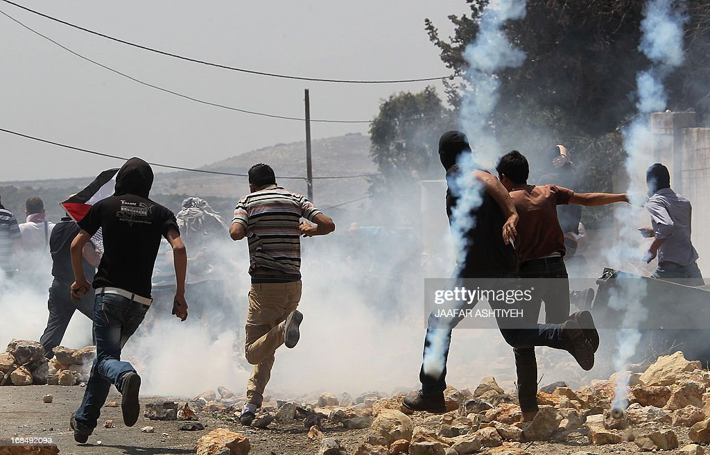 Palestinian demonstrators run for cover amidst tear gas smoke fired by Israeli troops during clashes following a protest against the expropriation of Palestinian land by Israel in the village of Kfar Qaddum near Nablus in the occupied West Bank on May 10, 2013.