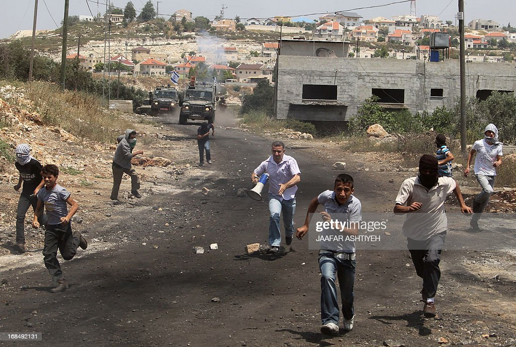 Palestinian demonstrators run for cover during clashes with Israeli troops following a protest against the expropriation of Palestinian land by Israel in the village of Kfar Qaddum near Nablus in the occupied West Bank on May 10, 2013.