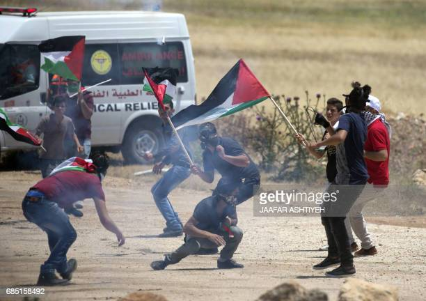 TOPSHOT Palestinian demonstrators run for cover during clashes with Israeli forces following a protest in support of Palestinian prisoners on hunger...