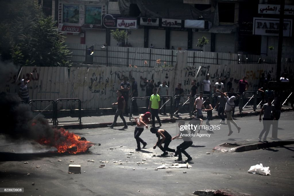 Palestinian demonstrators throw stones and burn tyres in response to Israeli security forces' intervention with tear gas bombs and plastic bullets during a demonstration to protest Israeli violations and restrictions on Al Aqsa Mosque, in Hebron, West Bank on July 28, 2017.