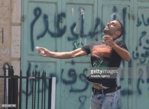Palestinian demonstrators throw stones in response to Israeli security forces' intervention with tear gas bomb during a demonstration to protest...