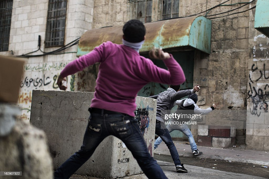 Palestinian demonstrators throw stones towards Israeli troops during clashes in the old city of Hebron on March 1, 2013 following a protest demanding the reopening of Shuhada Street, the one-time heart of the city, which has been declared off-limits to Palestinians and can only be used by Jewish settlers.