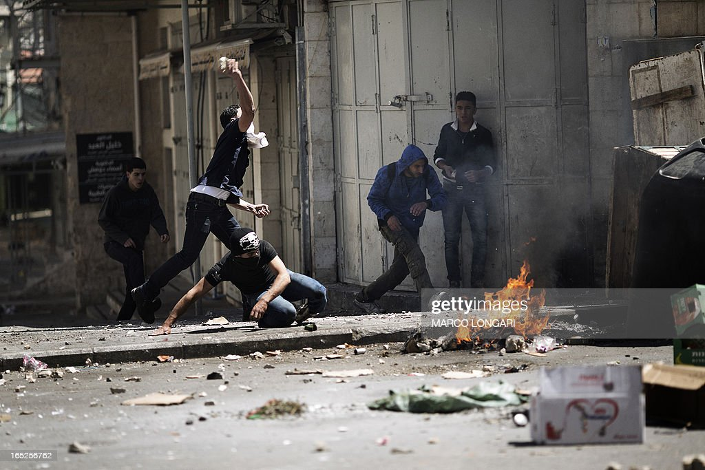 Palestinian demonstrators throw stones towards Israeli troops during clashes in the West Bank city of Hebron following the death of a Palestinian prisoner on April 2, 2013. The Palestinian leadership blamed Israel for the death of Maisara Abu Hamdiyeh, a long-term prisoner with cancer, hiking tensions over a tinderbox issue closely followed on the Palestinian street.