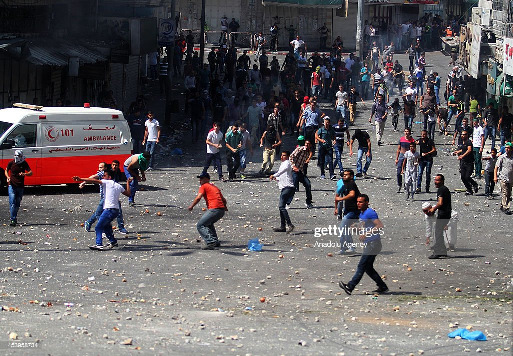 Palestinian demonstrators throw stones towards Palestinian security forces following a protest to show support for resistance movement Hamas in Hebron, West Bank on August 22, 2014.