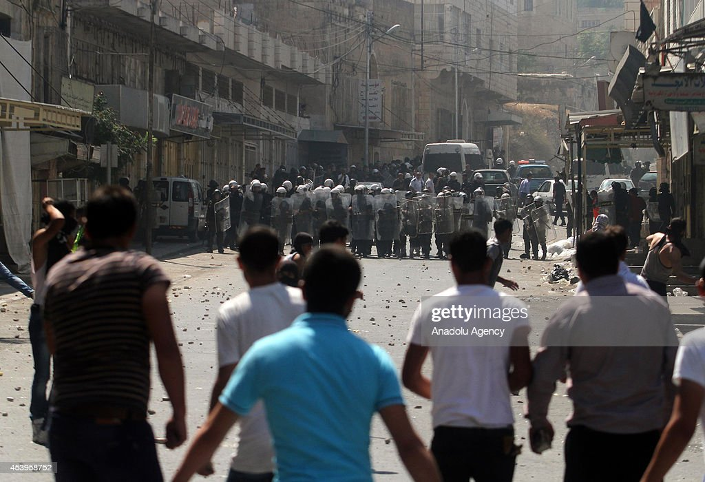 Palestinian demonstrators throw stones towards Palestinian security forces as they block the road following a protest to show support for resistance movement Hamas in Hebron, West Bank on August 22, 2014.