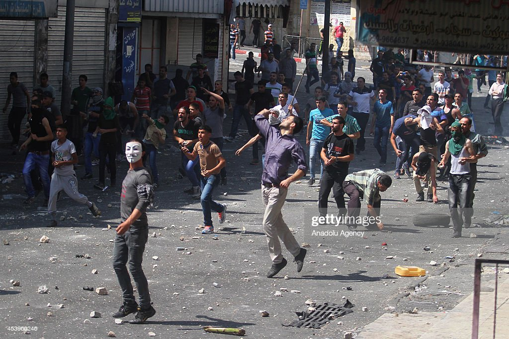 Palestinian demonstrators throw stones towards security forces following a protest to show support for resistance movement Hamas in Hebron, West Bank on August 22, 2014.