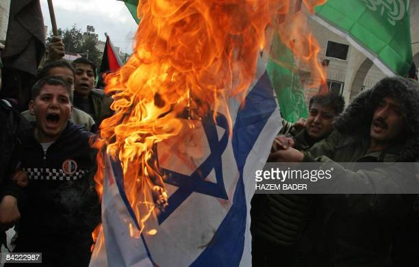 Palestinian demonstrators wave Hamas's green flag as they burn an Israeli flag during a demonstration in the West Bank city of Hebron on January 9...