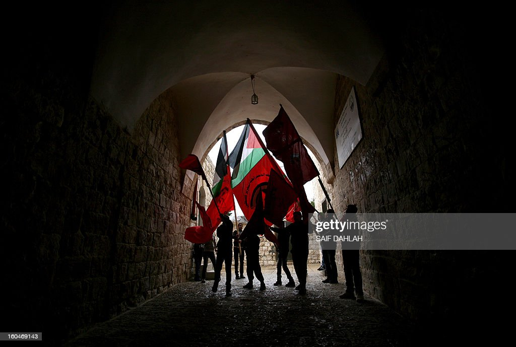 Palestinian demonstrators wave their national flag (C) and the red party flag of the Democratic Front for the Liberation of Palestine (DFLP) under a covered passage during a protest in support with Palestinian prisoners on hunger strike in Israeli jails and against administrative detention in the northern West Bank village of Araba, near Jenin, on February 1, 2013.