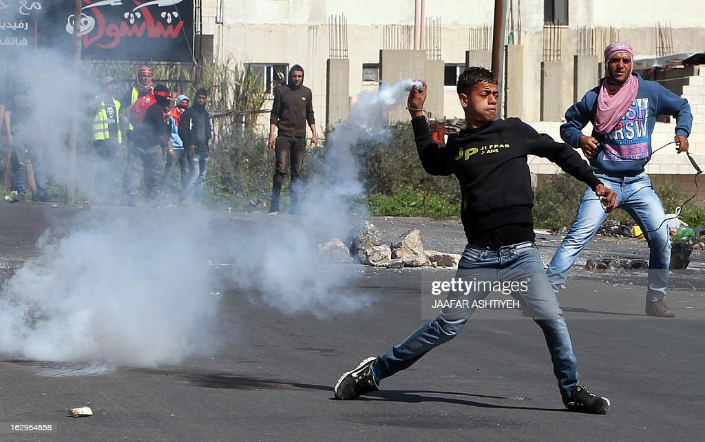 A Palestinian demonstrrator hurls a smoke grenade back at Israeli soldiers during a rally marking the 46th anniversary of the foundation of the Popular Front for the Liberation of Palestine (PFLP), a Palestinian Marxist-Leninist and revolutionary leftist organization founded in 1967, as clashes broke out between Israeli security and protesters in the northern city of Nablus, in the Israeli occupied West Bank, on March 2, 2013.