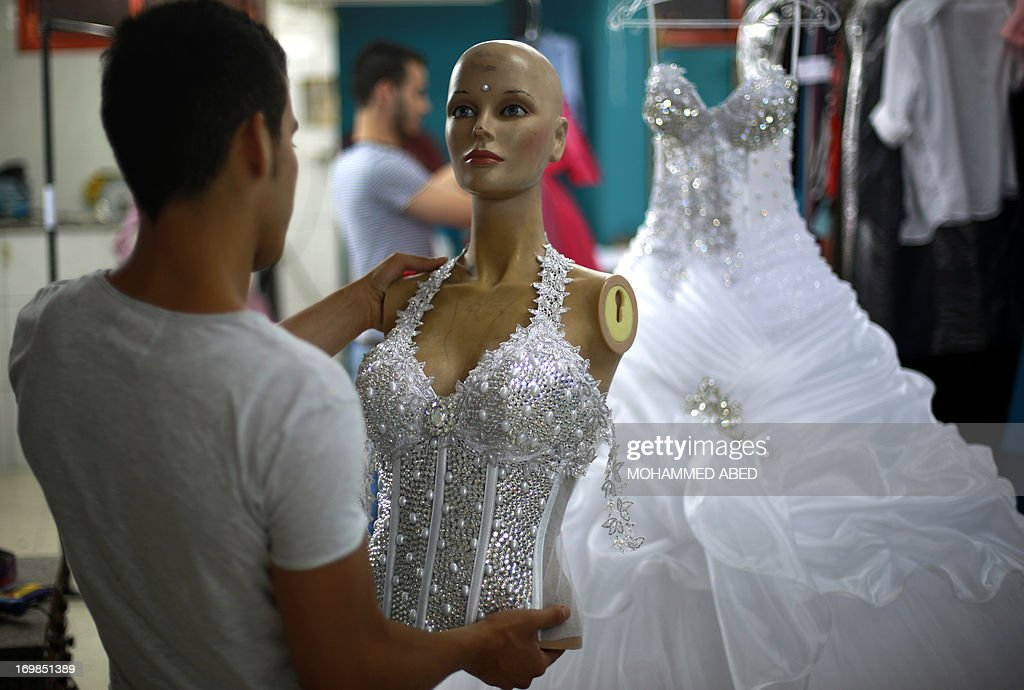 A Palestinian designer from the al-Ashi family holds up the bodice of a wedding gown at their atelier in Gaza City on June 3, 2013. The family started their own clothing line -wedding dresses and evening gowns- due to the difficulties and cost of smuggling and importing items into the Gaza Strip, either through legitimate crossings controlled by Israel to the north and east and Egypt in the south, or through smuggling tunnels dug under their southern border with Egypt and when the Egyptian border is closed.