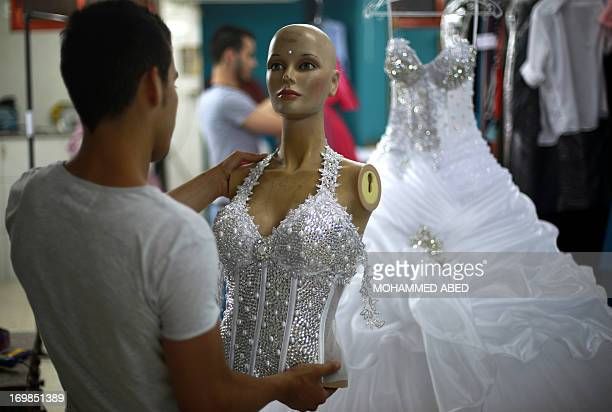 A Palestinian designer from the alAshi family holds up the bodice of a wedding gown at their atelier in Gaza City on June 3 2013 The family started...